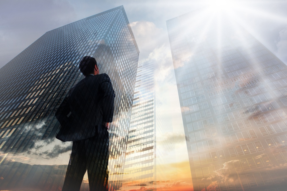 Businessman standing with hands on hips against low angle view of skyscrapers at sunset.jpeg